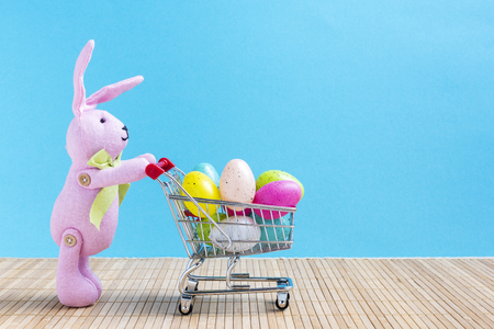 Easter bunny with shopping cart and colorful eggs in front of a blue background
