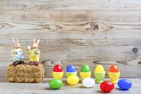 Easter eggs with egg cups and bunnies in front of a wood background