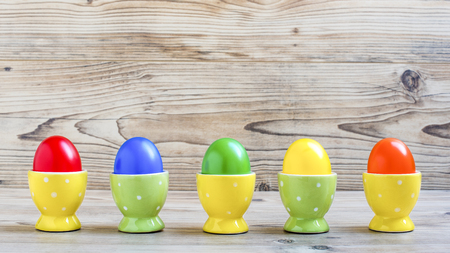 Easter eggs with egg cups in front of a wood background