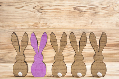 Five easter bunnies in front of a wood background