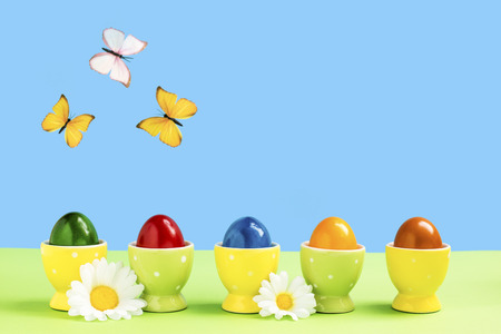 Five eggcups with colorful easter eggs and butterflies with flowers Фото со стока