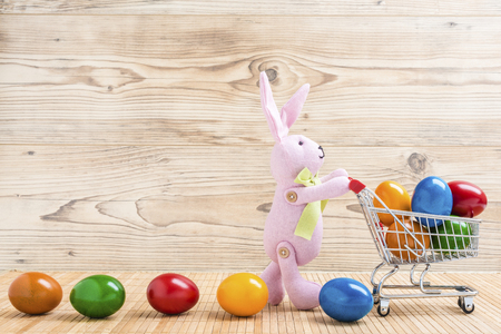 An easter bunny with shopping cart and colorful eggs in front of a wood background