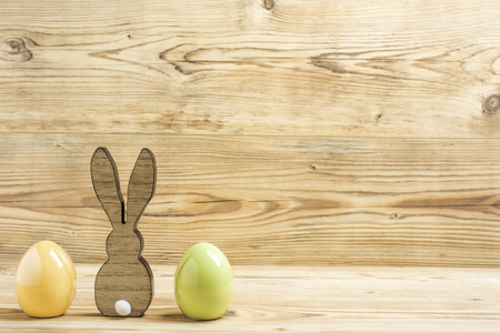 An easter bunny with two easter eggs in front of a wood background
