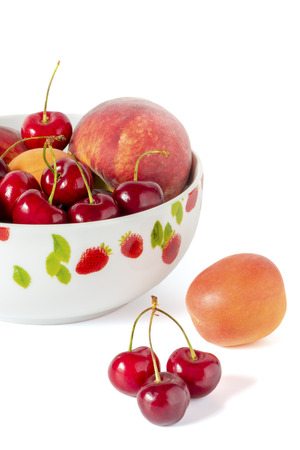 A bowl with peaches and cherries in front of a white background