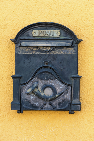 An old nostalgic metal mailbox on a yellow house wall
