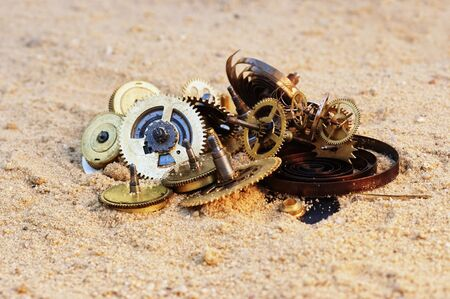parts of clockwork mechanism on the sand photo