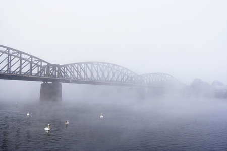 Prague railway bridge in the foggy day photo