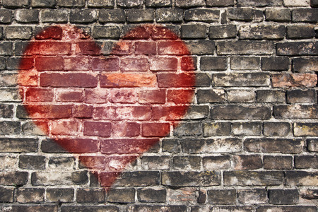 brick sign: heart on the old broken brick wall Stock Photo