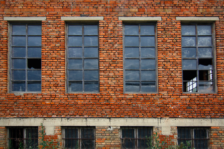 dilapidated wall: Old brick wall with broken windows Stock Photo