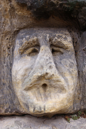 rock formation: Scary Stone Heads - rock sculptures of giant heads Stock Photo