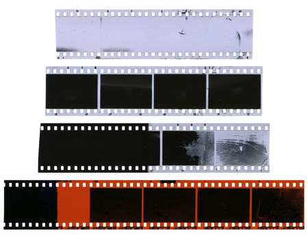 Old, used, dusty and scratched celluloid film strips isolated on white background
