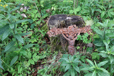 Old rusty cross with Jesus lost in the woods