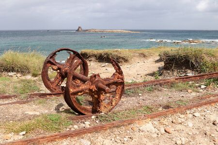 Remains after of granite mining on island Ile Grande in Pleumeur-Bodou in Brittany, France - rails and rusty wheels