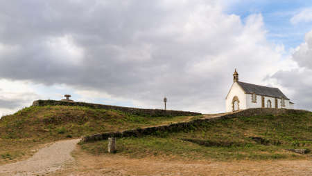 Megalithic grave mound Tumulus of St Michel with chapel of Saint Michel near Carnac in Brittany, France. It is the largest grave mound in Europe.