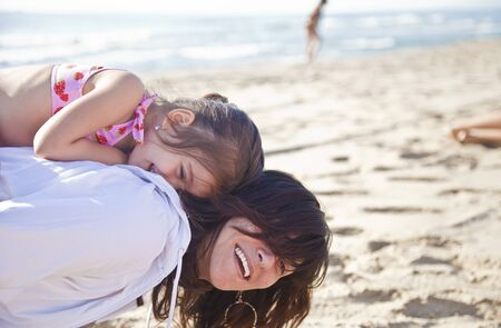 Mom plays with her daughter on the beach