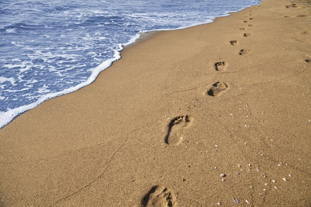 Footsteps of a man who walks on the beach by the sea photo