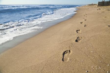 huellas de pies: Huellas de un hombre que camina en la playa junto al mar