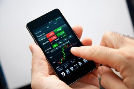 Businessman den Fortschritt ihres Handelns online mit seinem Smartphone