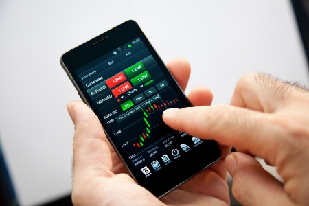 stock trading: Businessman monitor the progress of their actions online with his smartphone