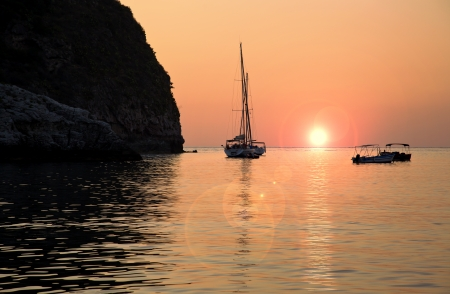 sailing boat moored near the coast at sunset Stockfoto