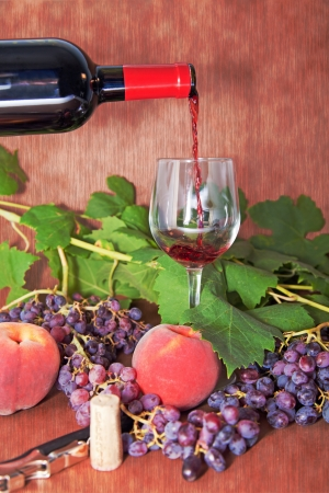 Composition of wine with a bottle and a glass of wine between leaves and fruit