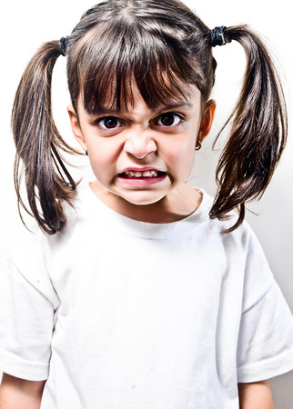 little girl with pigtails very angry isolated on white Stock Photo