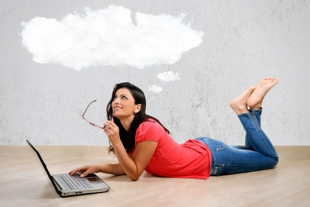 Beautiful Caucasian woman smiles thinking in front of his laptop. Concept of the Internet. Woman lying full length isolated on white background