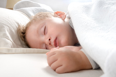 little blond boy, relaxed sleeping on her bed wrapped in a soft blanket