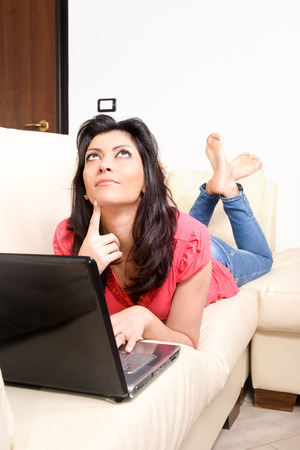 smiling young woman lying on the couch, surfing the internet with her laptop computer. Concept of relaxation Stock Photo - 24238120