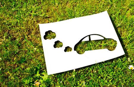 silhouette voiture: Blanc papier découpé dans la forme d'une voiture sur un fond d'herbe concept énergétique renouvelable
