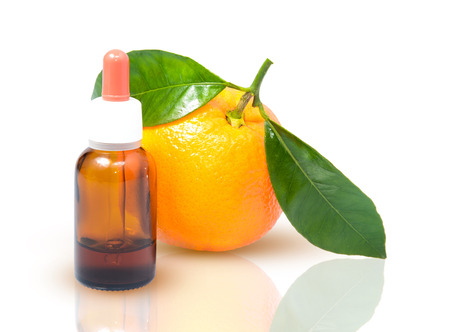 Orange with green leaves and a bottle with dropper isolated on a white
