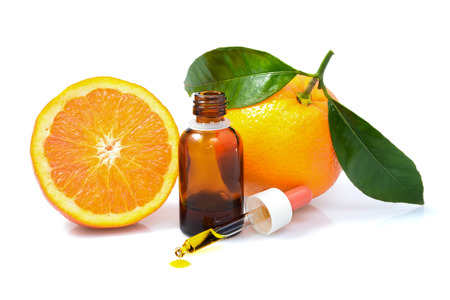 perfume oil: Orange with green leaves and a bottle with dropper isolated on a white Stock Photo