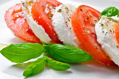 caprese salad: Caprese Salad. Tomato and Mozzarella slices with basil leaves.