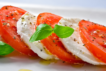 Caprese Salad. Tomato and Mozzarella slices with basil leaves.