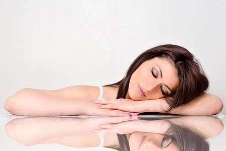 donna: Beautiful face skincare bellezza donna sdraiata con riflessione a specchio isolato su sfondo bianco