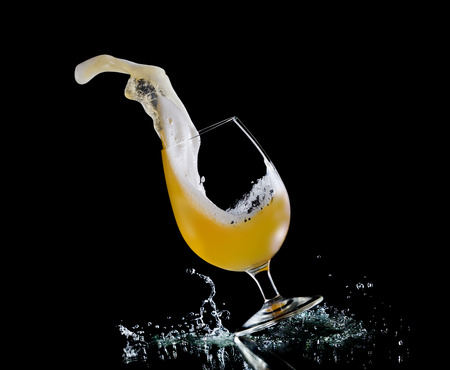 Falling glass of beer on dark background. Stock Photo
