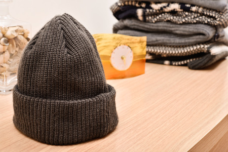 eg: woolen cap on a wooden table with sweaters background