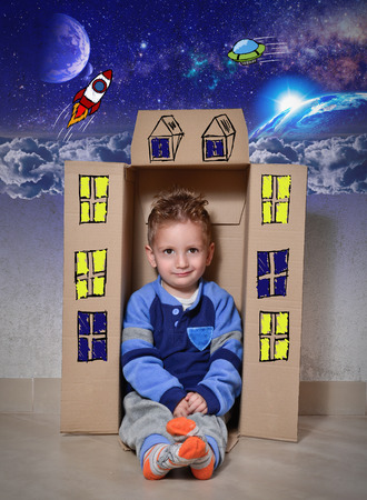 Child playing with a cardboard box. Imagine space adventures