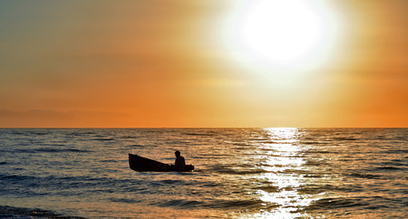 Silhouette of a little fishing boat on sunset.