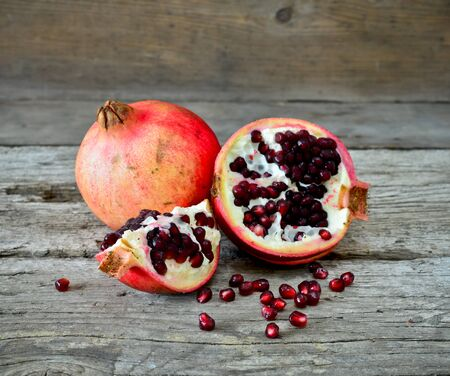 closeup of a pomegranate on a rustic wooden table Stock Photo