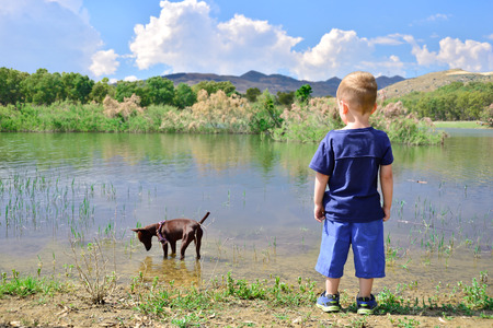 Child on the shore of Lake pozzillo, looking her dog in water.