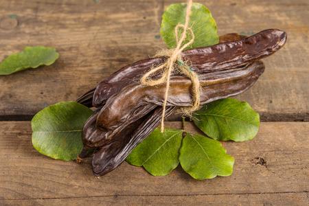 carob: Raw fruits Carob on old wooden background