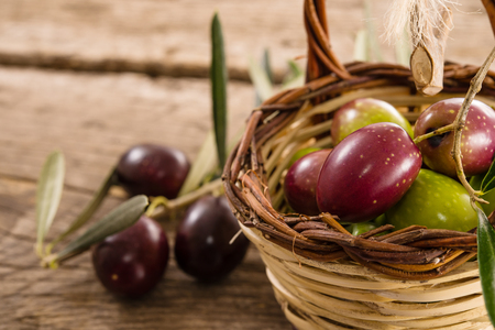 tastes: fresh olives in a basket, placed on a rustic wooden table. Olives from Sicily, Italy Stock Photo