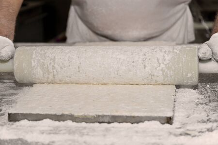 roll out: Close Up Of Hands Using Rolling Pin To Roll Out Pastry