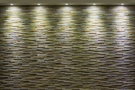 illuminate: Stone wall with spotlights that illuminate from above