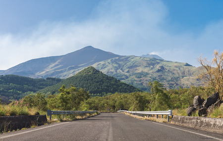 Road on the south side of Mount Etna, with central crater on background