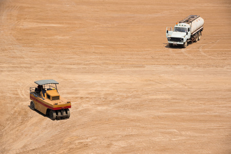 compactor: High View Of Space Of Construction Site With Compactor And Water Trunk