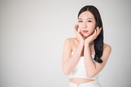 Hermosa mujer asiática con cuidado de la piel o concepto de cuidado facial aislado sobre fondo blanco, concepto de cirugía de tratamiento de belleza. El cuidado facial y el cuidado de la piel son parte del cuidado de la belleza para la mujer asiática.