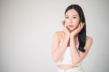 Mooie Aziatische vrouw met huidzorg of gezichtsverzorgingconcept die op witte achtergrond, de chirurgieconcept van de schoonheidsbehandeling wordt geïsoleerd. Gezichtsverzorging en huidverzorging is het onderdeel van schoonheidsverzorging voor Aziatische vrouwen.