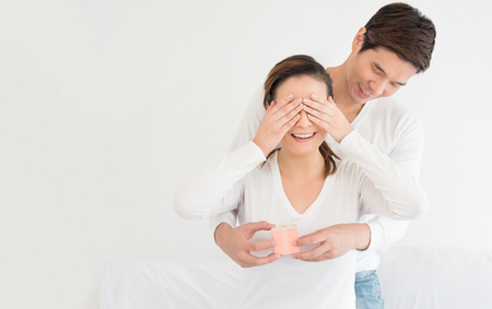 Asian lover or love couple wedding proposal concept, Asian man is surprising his girlfriend by proposing wedding ring gift box on white background, Romantic love moment concept.